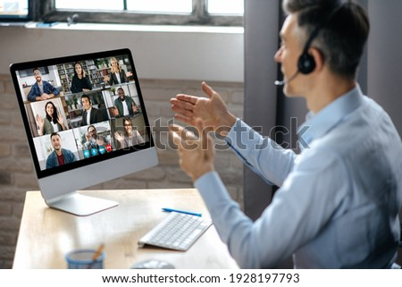Virtuak business meeting online. Successful businessman is negotiating with multiracial business partners on a video conference using a computer while sitting at his workplace