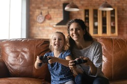 Virtual battle. School age girl sit on sofa play video game with elder adult sister laugh yell enjoy activity. Happy young mother and small daughter spend free time together relax on weekend at home