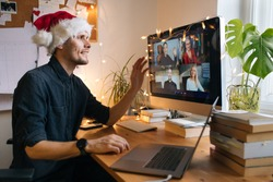 Virtual Christmas day house party. Man smiling wearing Santa hat Business video conferencing Young man having video call via computer in the home office Online team meeting video conference calling.