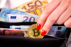 Virtual cryptocurrency money Bitcoin golden coins in the left hand of a woman with red nail polish and a purse. The future of money. Euro banknotes.