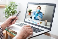 Virtual doctor visit,telemedicine healthcare concept,young female doctor giving advice over laptop computer screen to elderly woman,hands holding glasses  medical worker on display,remote appointment