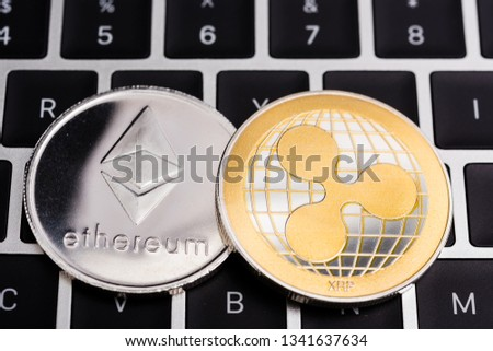Virtual Ethereum and ripple XRP coins currency finance money on computer laptop keyboard #1341637634