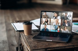 Virtual meeting online. Video conference by laptop. Online business meeting. On the laptop screen, people who gathered in a video conference to work on-line, near stands a cup of coffee