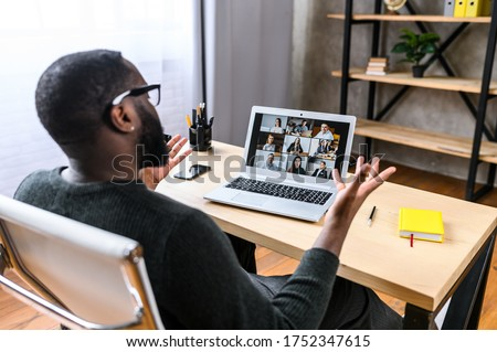 Virtual meeting with many people together. African-American young guy talking online with employees via video connection. Multiracial team. Back view