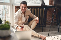 Virtual party. Pleased man lifting a glass of red wine in front of his laptop