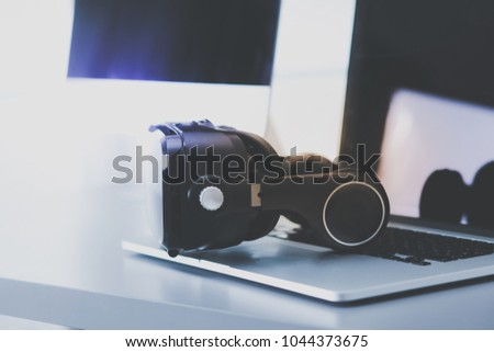 Virtual reality goggles on desk with laptop. business. 3d technology #1044373675
