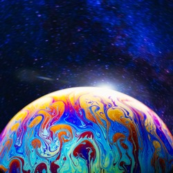 Virtual reality space with abstract multicolor psychedelic planet against starry sky. Closeup of soap bubble like an alien planet in cosmos
