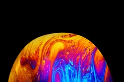 Virtual reality space with abstract multicolor psychedelic planet. Closeup Soap bubble like an alien planet on black background.