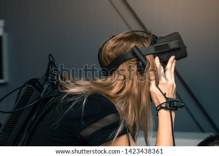 Virtual reality with full immersion. The girl is wearing VR glasses on her head, she has a video camera and a motion sensor on her hand and backpack #1423438361