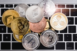 Virtual ripple XRP, Ethereum and Bitcoin coins currency finance money stack together on keyboard of laptop computer, cryptocurrency concept
