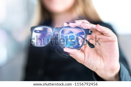Virtual screen smart glasses with futuristic high tech interface. Woman holding spectacles with nanotech interface. Augmented reality vision with modern eyewear. Future innovation with IOT and VR. #1156792456