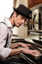 Virtuoso playing piano. Side view of handsome young men playing piano