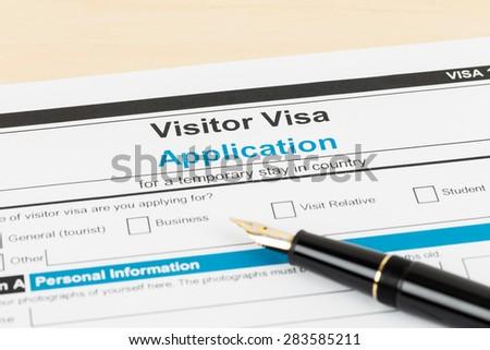 Visa application form with pen; form is mock-up