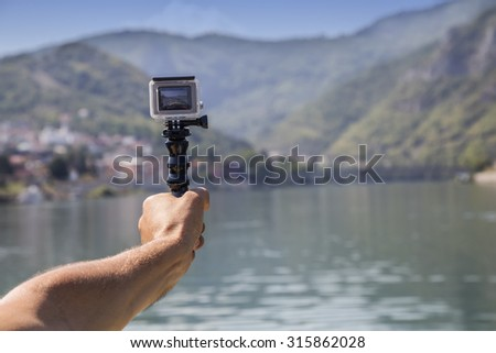 VISEGRAD, SERBIA - SEPTEMBER 03, 2015: Hand holding GoPro Hero 4 Silver camera, action camera in hand with waterproof case. Made with shallow depth of field.