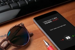 Vishing (voice phishing) concept, a smartphone on a table next to computer keyboard and sunglasses show an unknown caller call with vishing alert and a reminder to not share personal bank data