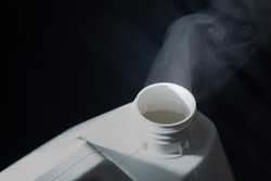 Visible smoke or fumes or chemicals drifting and curling from the cracked open lid of a 5l plastic container or tub
