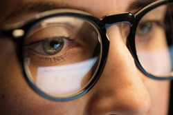 vision, business and education concept - close up of woman eyes in glasses looking at computer screen