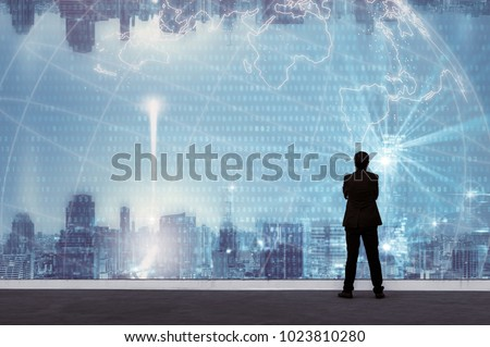 Vision concept. Successful businessman standing with hands crossed on chest, On top of building and looking through Cityscape Skyline Night Light. #1023810280