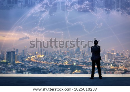 Vision concept. Successful businessman standing with hands crossed on chest, On top of building and looking through Cityscape Skyline Night Light. #1025018239