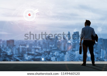 Vision concept, Young business man on the roof of the building and look through to find out goals and success with ambition and commitment to success in the job. #1149460520