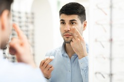 Vision Correction Concept. Portrait of handsome man applying soft contacts, looking in mirror, holding plastic contact eye lenses container in hand, view over the shoulder. Eyecare and medicine