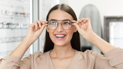 Vision Correction Concept. Portrait of happy beautiful woman trying on new eyeglasses in optics store, banner, copy space. Smiling lady client wearing spectacles, choosing and picking frame