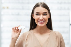 Vision Correction Concept. Portrait of smiling lady showing plastic container with contact eye lenses to camera, standing in optics store with case. Shortsighted Optometry Female Client