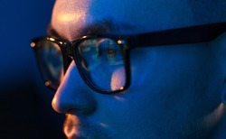 vision, hacking and technology concept - close up of hacker eyes in glasses looking at computer screen in darkness