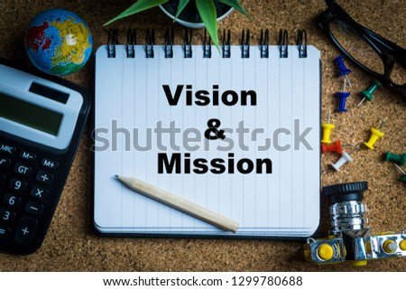 VISION & MISSION inscription written on book with globe,eyeglasses, calculator, camera, pencil and vase on wooden background with selective focus and crop fragment. Business and education concept Stock fotó ©