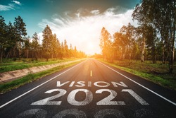 Vision 2021 written on highway road in the middle of empty asphalt road at golden sunset and beautiful blue sky. Concept for new year 2021.