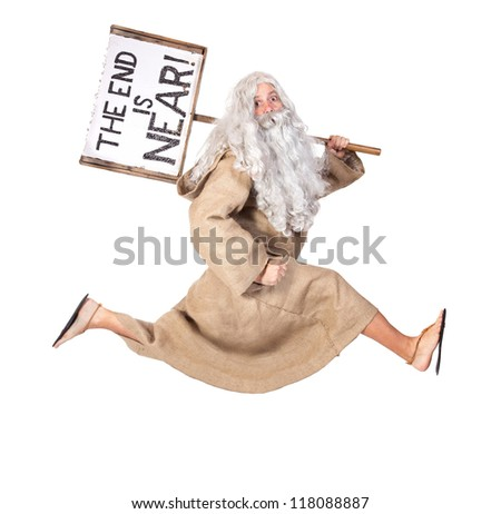 Visionary runs with a sign on his shoulder. Bearded monk rushes with the sign of the end of the world. Prophet runs with the board The end is near isolated on white background. The end is near.