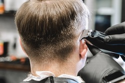 Visit to the barbershop. Hairdresser, barber shaves client's temples,sides with hair clipper. Young stylish man makes fashionable haircut.Customer sitting in dark men's beauty salon covered with cape.