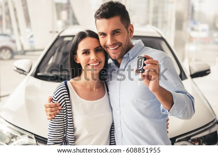 Visiting car dealership. Beautiful couple is holding a key of their new car, looking at camera and smiling