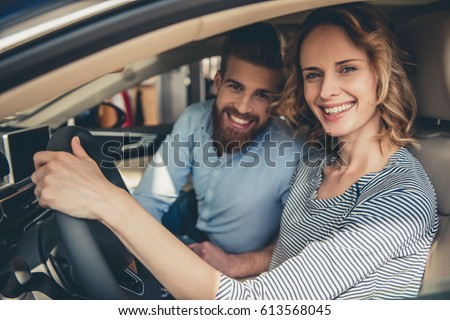 Visiting car dealership. Beautiful couple is looking at camera and smiling while sitting in their new car #613568045