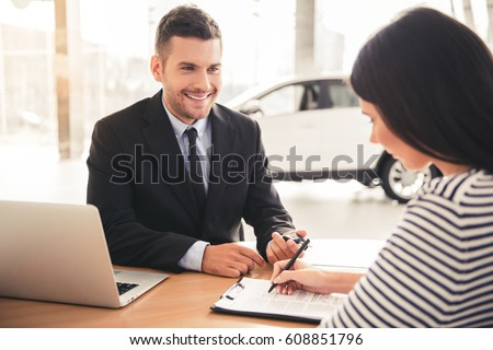 Visiting car dealership. Handsome sales manager is smiling while beautiful client is signing papers