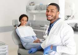 Visiting dentist. Black dentist doctor and female patient in chair smiling at camera, clinic interior