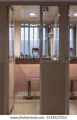 Visiting room or vis a vis where prisoners receive visits from their relatives and speak through armored glass #1518527012