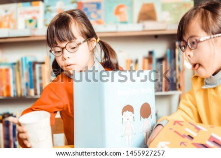 Visiting special school . Unusual young girls sitting together and observing informative book about self-knowledge