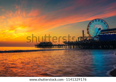 Visitors enjoy scenic sunset above Santa Monica Pier in Los Angeles, California.