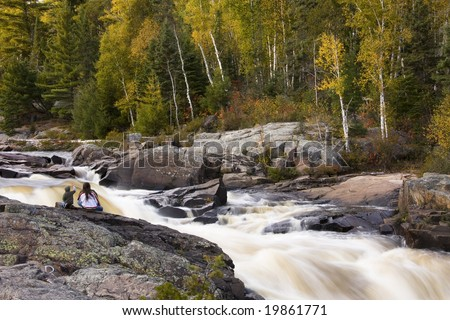 Visitors to local waterfalls on Current River admiring thundering water and fall colors. The area is called Cascades Conservation Area and is located in Thunder Bay, Ontario.
