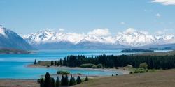 Vista with beautiful alpine scenery, turquoise glacier lake with snowy mountains in backdrop. Shot at Lake Tekapo, New Zealand