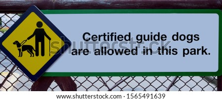 Visual description, guide dog sign for visually impaired on chain link fence