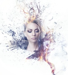 Visual digital art. Fantasy woman portrait. Girl in smoke and fire dressed in black wings and a crown of dry burning tree branches. Black feathers and particles flying out of her, ravens soar