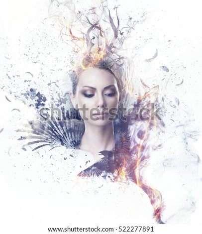 Stock Photo Visual digital art. Fantasy woman portrait. Girl in smoke and fire dressed in black wings and a crown of dry burning tree branches. Black feathers and particles flying out of her, ravens soar