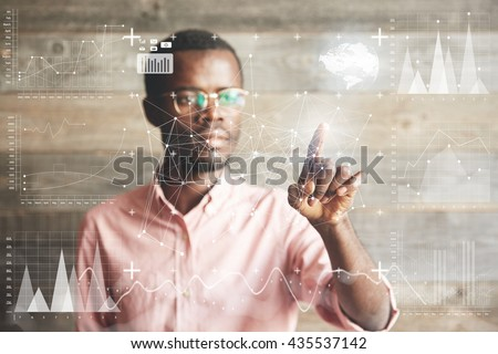 Visual effects. Future technology touch screen interface. Handsome African American businessman in shirt touching screen interface, drawing a chart in futuristic office. Selective focus on the hand