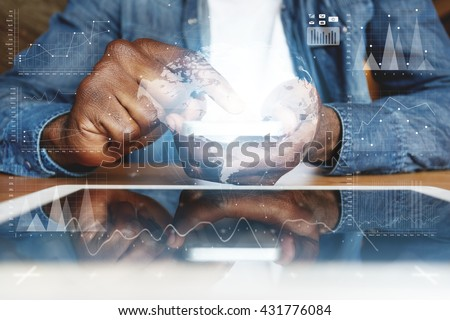 Visual effects. Graphic icons. People and future technology concept. Cropped shot of African American young man in denim jacket, touching electronic gadget with reflective touchscreen surface