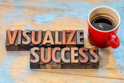 visualize success banner  - text in vintage letterpress wood type blocks stained by color inks against grunge wood with a cup of coffee