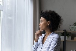 Visualizing perspectives. Serious contemplative black businesswoman young leader look at office window touch chin deep in thoughts solve business problem in mind create new sales strategy. Copy space
