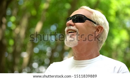 Visually impaired man in sunglasses listening nature sounds, heightened senses