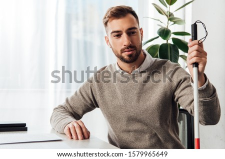 Visually impaired man in wireless earphones holding walking stick at table Foto stock ©